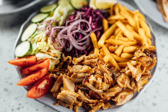 Doner Kebab on plate with vegetables fries and souce, grilled meat on plate