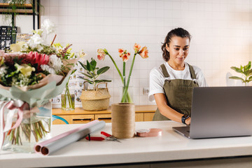 Woman wearing apron working in her flower shop. Young businesswoman typing on laptop indoors. - fototapety na wymiar