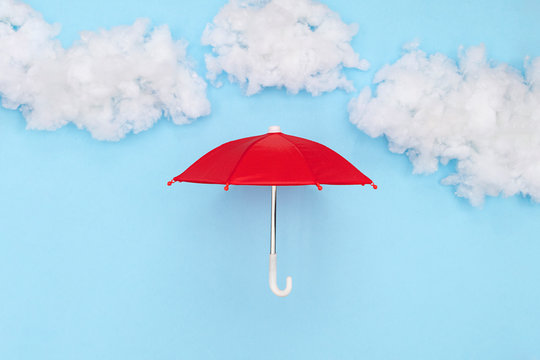 Red umbrella place under a puffy cotton stuffing on a sky blue background