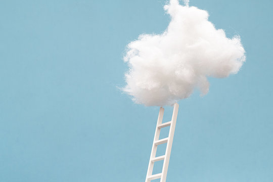ladder leading up to a puffy cotton cloud on a blue background.