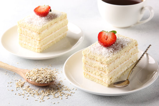 Dessert. White biscuit cake with cream and coconut shavings on white plate with spoon. A ?up of coffee and strawberry on a light background. Background image, copy space