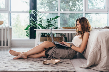 Girl is sitting relaxed on the floor with a laptop on her lap