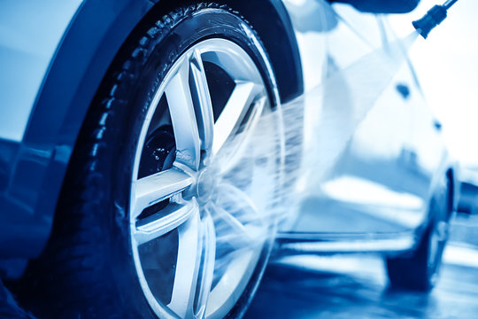 Car wheel wash. Cleaning with water jet. Cars rim or alloy washing close up.