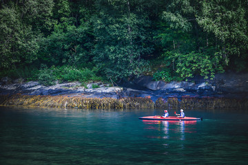 Kayaking couple ride along the river with panoramic beautiful deep forest and waterfall in norway near blue river or ocean. Wall mural