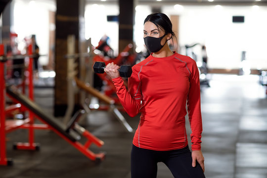 Coronavirus covid-19 prevention, fitness girl with a medical mask holding a dumbbell . Fighting viruses.