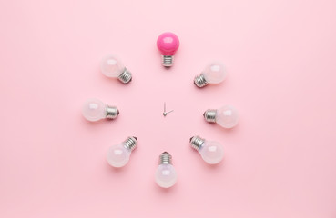Creative clock made of light bulbs on color background