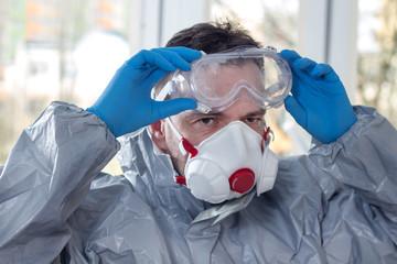 Obraz Zmęczony , spocony mężczyzna ubrany w kombinezon ochronny i maskę ochronną na twarz zdejmuje gogle ochronne i rozbiera się po skończonej pracy. - fototapety do salonu