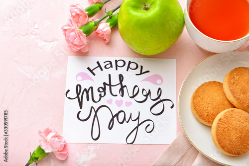 """Card with text """"Happy Mother's day"""" and tasty breakfast on color background"""