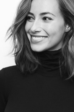 Portrait of young happy woman in black and white with a big smile on her face looking at one side