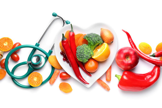 Plate with healthy products and stethoscope on white background