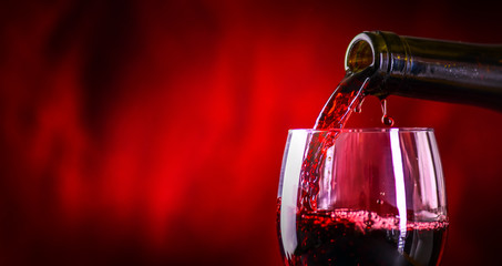 Pouring red wine into the glass against rustic background.