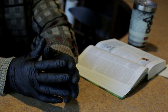 A church volunteer wears gloves next to an open Bible, as parishioners watch Sunday service on a screen in a lobby, at Eastside Church in Bothell
