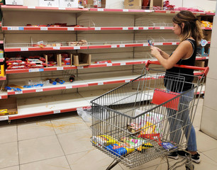 A woman takes a picture of noodles on the floor in front of empty pasta shelves at a supermarket, as people began stockpiling food following the coronavirus outbreak, in Buenos Aires