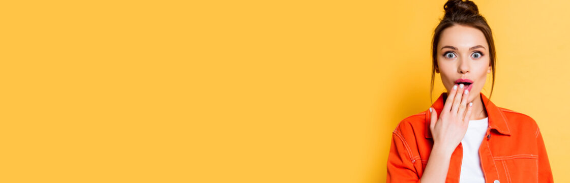 panoramic shot of shocked girl looking at camera while covering mouth with hand on yellow background