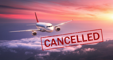 Airplane and flight cancellation. Canceled flights in Europe, Asia and USA airports. Travel cancelled because of pandemic of coronavirus. Background of flying passenger aircraft with text. Covid-19 Fotomurales
