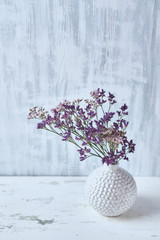 Dry violet flowers in a white vase. Still life. Copy space