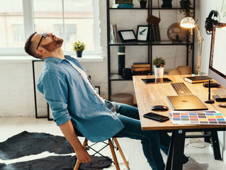 Exhausted man sitting at table with gadgets.