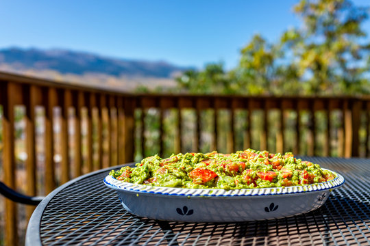 Metal table on deck mountain view and large big guacamole dish with tomatoes in serving tray with green avocado color for party platter