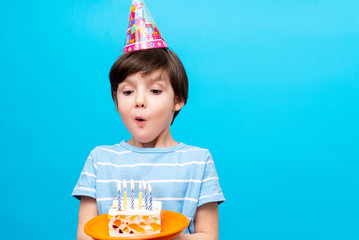Caucasian boy emotionally blowing candles on a birthday cake, wearing a blue t-shirt and a holiday hat on his head, standing on a blue studio background. holiday and birthday with place for text