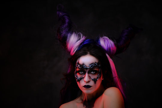 Close up photo of a mystic young girl in a magic creature cosplay, wearing dark banshee make-up, contact lenses and violet horns, looking demonic posing in a dark studio with red lights