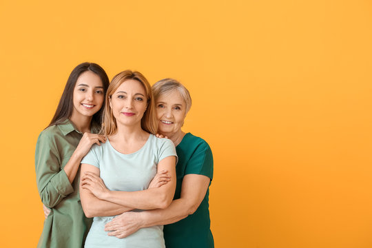 Portrait of mature woman with her adult daughter and mother on color background