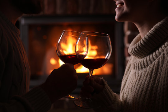 Lovely couple with glasses of wine near fireplace at home, closeup. Winter vacation