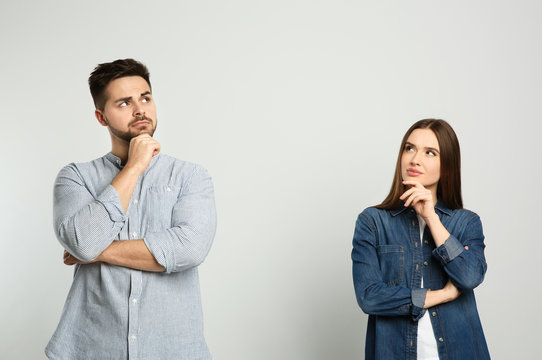 Pensive couple on light background. Thinking about answer for question