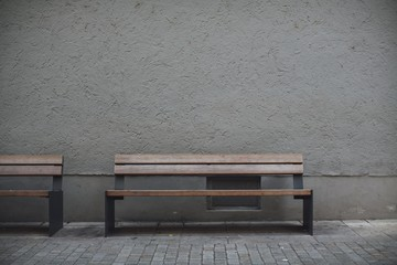 Wall Murals Wall Closeup shot of wooden benches against a grey stone wall in an empty street