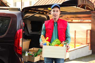 Courier holding crate with products near car outdoors. Food delivery service