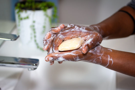 close up of black african australian woman washing hands with soap in sink