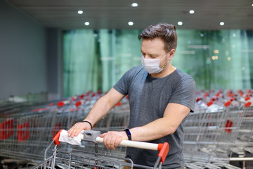 Man wearing disposable medical face mask wipes the shopping cart handle with a disinfecting cloth in supermarket. Safety during coronavirus outbreak.