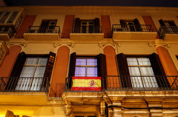Lit balconies of a building and a Spanish flag are seen as people remain confined inside their homes during partial lockdown as part of a 15-day state of emergency to combat the coronavirus outbreak in Malaga