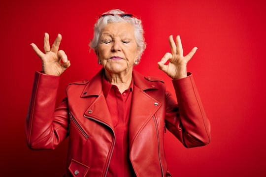 Senior beautiful grey-haired woman wearing casual red jacket and sunglasses relax and smiling with eyes closed doing meditation gesture with fingers. Yoga concept.
