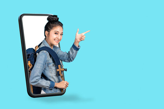 Smartphone pop up for advertising.asian woman travel backpacker standing pointing hands to copyspace.girl smiling wearing casual jeans shirt and finger pointing.Digital marketing online cencept.