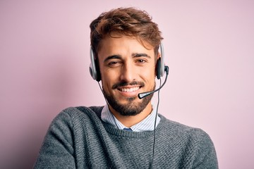 Young call center agent man with beard wearing headset over isolated pink background happy face smiling with crossed arms looking at the camera. Positive person.