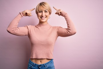 Young blonde woman with short hair wearing casual turtleneck sweater over pink background smiling...