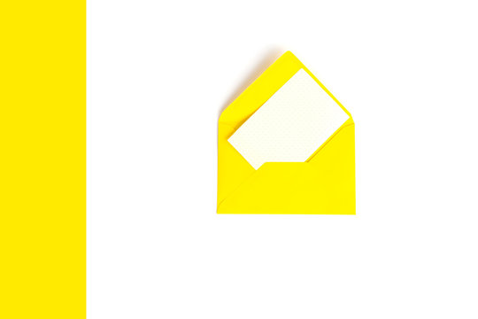 A yellow envelope and a blank white card on a geometric background in yellow and white color. Newsletter concept. Template mock up with copy space. Top view.