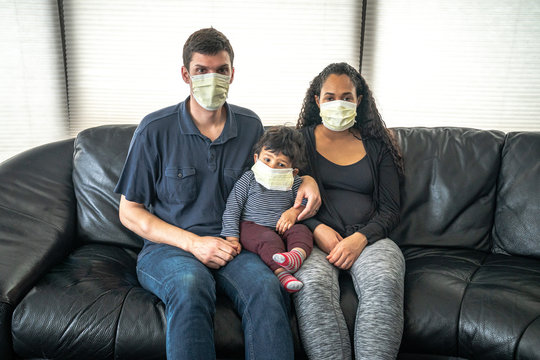 A mixed family sits on a black leather sofa with father and mother holding their infant son all wearing medical face masks in hopes of preventing getting sick from caronavirus or COVID-19.