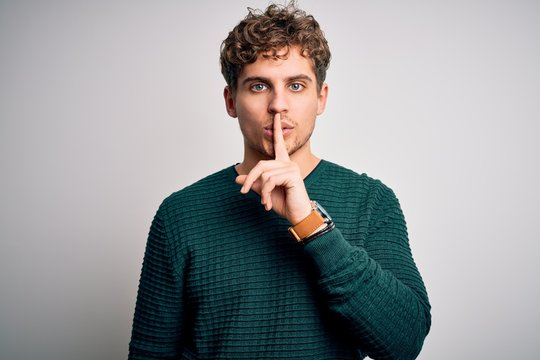 Young blond handsome man with curly hair wearing green sweater over white background asking to be quiet with finger on lips. Silence and secret concept.