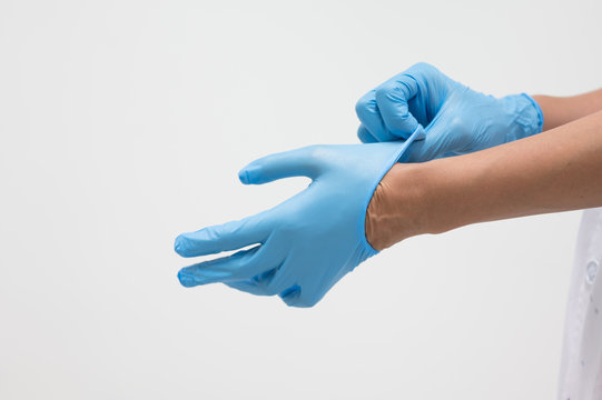 Woman doctor putting blue latex medical gloves on white background.Surgeon wearing gloves before surgery at operating room.Risk and infection control concept.