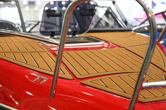 Red motor boat bow deck close up with brown marine teak coating, railing and opened porthole window