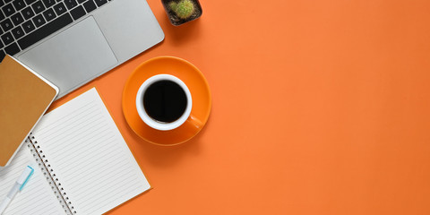 Top view image of Colorful working table. Flat lay Computer laptop, Cactus, Notebook, Diary, Pen and Coffee cup. Colorful workplace concept.