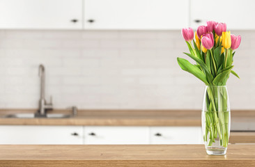 Bouquet of beautiful tulips on the kitchen table top on blur kitchen background with place for...