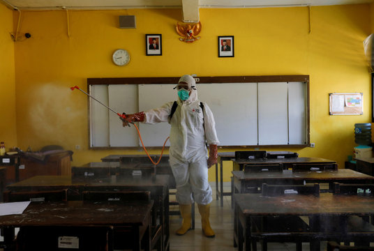 A volunteer from Indonesia's Red Cross wearing a protective suit sprays disinfectant inside the classroom of a school closed amid the spread of coronavirus in Jakarta