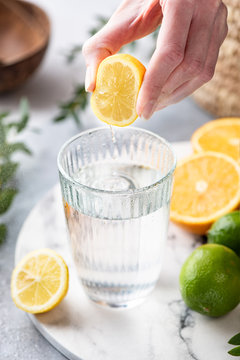 Lemon citrus water in glass. Woman hand squeeze lemon in glass of fresh clean water. Refreshing cold summer drink Lemonade