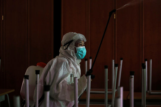 A volunteer from Indonesia's Red Cross wearing protective suit sprays disinfectant at the classroom of a school closed amid the spread of coronavirus (COVID-19) in Jakarta