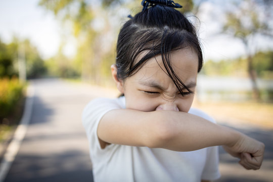 Asian child girl sneezing,coughing into her arm or elbow to prevent spread Covid-19,Coronavirus,avoid sneeze on hand,sick woman covering nose and mouth with her arm from dusty,allergies,air pollution