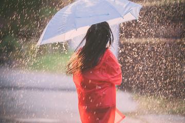 Asian children spreading umbrellas playing in the rain, she is wearing rainwear. Fotobehang