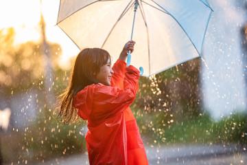 Asian children spreading umbrellas playing in the rain, she is wearing rainwear.