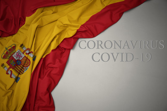 waving national flag of spain with text coronavirus covid-19 on a gray background.